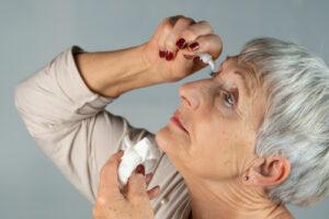 A woman applying eye drops