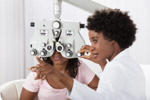 optometrist giving eye exam to patient